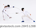 The woman and man wearing fencing suit practicing 28451288