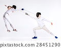 The woman and man wearing fencing suit practicing 28451290