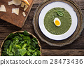 Portion spinach soup with egg and cheese parmesan. 28473436