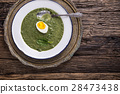 Portion spinach soup with egg and cheese parmesan. 28473438
