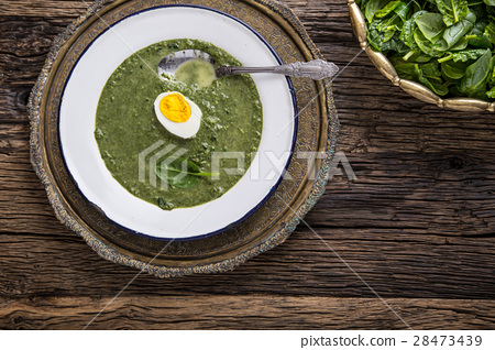 Portion spinach soup with egg and cheese parmesan. 28473439