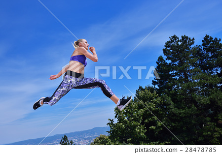 Young woman joyfully jumping in Park 28478785