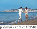 Couple walking on beach. Young happy interracial 28479588
