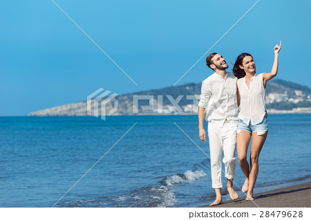 Couple walking on beach. Young happy interracial 28479628