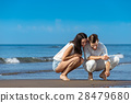 Romantic young couple draw shapes in the sand 28479680