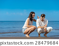 Romantic young couple draw shapes in the sand 28479684