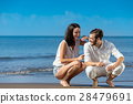 Romantic young couple draw shapes in the sand 28479691
