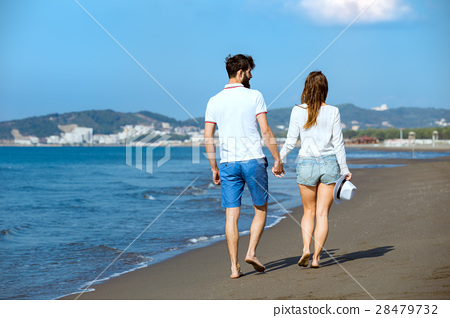 Couple walking on beach. Young happy interracial 28479732