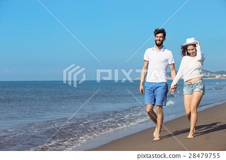 Couple walking on beach. Young happy interracial 28479755