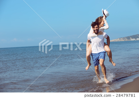 A guy carrying a girl on his back, at the beach 28479781