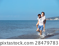 A guy carrying a girl on his back, at the beach 28479783