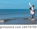 A guy carrying a girl on his back, at the beach 28479790