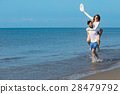 A guy carrying a girl on his back, at the beach 28479792