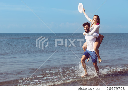 A guy carrying a girl on his back, at the beach 28479798