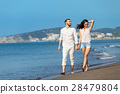 Couple walking on beach. Young happy interracial 28479804
