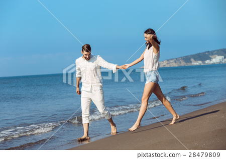 Couple walking on beach. Young happy interracial 28479809