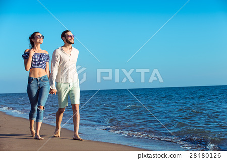 Couple walking on beach. Young happy interracial 28480126