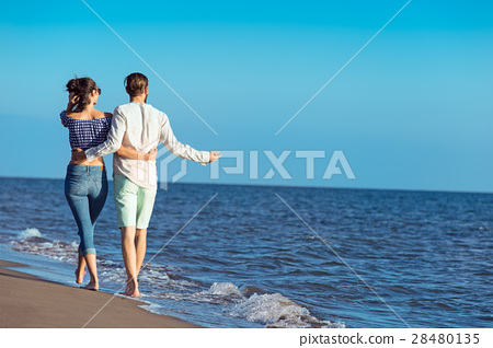 Couple walking on beach. Young happy interracial 28480135