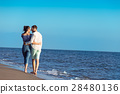 Couple walking on beach. Young happy interracial 28480136