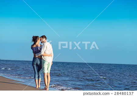 Couple walking on beach. Young happy interracial 28480137