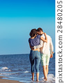 Couple walking on beach. Young happy interracial 28480205