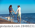 two young people running on the beach kissing and 28480231