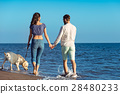 two young people running on the beach kissing and 28480233