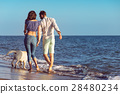two young people running on the beach kissing and 28480234