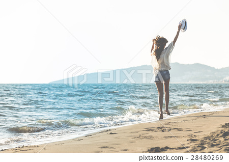Young female enjoying sunny day on tropical beach 28480269