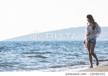 Young female enjoying sunny day on tropical beach 28480302