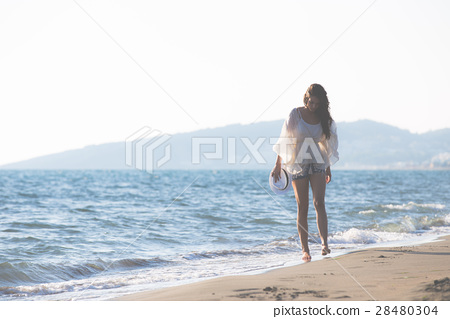 Young female enjoying sunny day on tropical beach 28480304