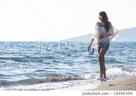 Young female enjoying sunny day on tropical beach 28480306