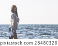 Young female enjoying sunny day on tropical beach 28480329