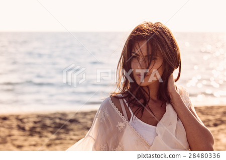 Young female enjoying sunny day on tropical beach 28480336