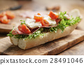 open sandwich with prosciutto, mozzarella and tomatoes on kitchen table 28491046