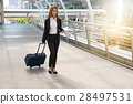 Businesswoman pulling a suitcase in a big city. 28497531