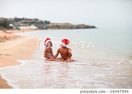 Caucasian kids sisters in santa hats on  beach  28497994