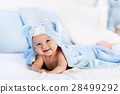Baby in towel after bath in bed 28499292
