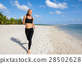 young fitness woman running at beach 28502628