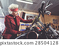 Thoughtful pensioner polishing bike in mechanic 28504128