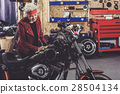 Smiling grandmother polishing bike in mechanic 28504134