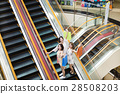 happy young woman on escalator in shopping mall 28508203