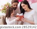 Cute positive mother and daughter holding a gift 28529142