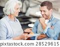 Pleasant aged woman presenting croissant 28529615