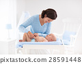Mother changing diaper to baby boy 28591448