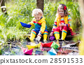 Kids playing with colorful paper boats in a park 28591533