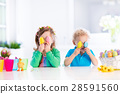 Kids with colorful Easter eggs on egg hunt 28591560