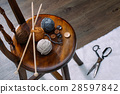 button and yarn ball on wooden chair 28597842