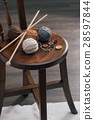 button and yarn ball on wooden chair 28597844