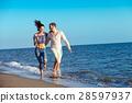 happy couple running on the beach 28597937